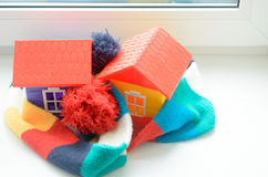 Toy house on the window sill wrapped in a scarf. Warming up the house. Stock Image