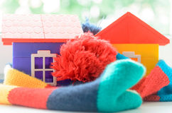 Toy house on the window sill wrapped in a scarf. Warming up the house. Royalty Free Stock Photos