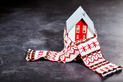 Toy house worming up with scarf. Little toy house wrapped with patterned knitted scarf standing isolated on dark surface Royalty Free Stock Photo