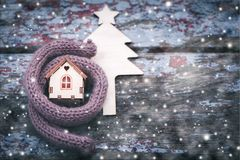 Toy house is wrapped in a warm scarf, it`s snowing. in the backg Stock Photo