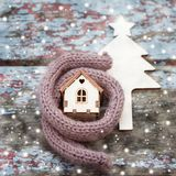 Toy house is wrapped in a warm scarf, it`s snowing. in the backg Stock Photos