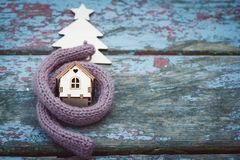 Toy house is wrapped in a warm scarf, it`s snowing. in the backg Royalty Free Stock Photos