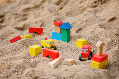 Toy houses and trucks made of colorful wooden bricks in sandbox Royalty Free Stock Photos