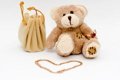 Toy and Jewelry. Stuffed bear with jewelry (necklace) beside it, jewelry pouch beside, isolated on white ibackground Stock Photography