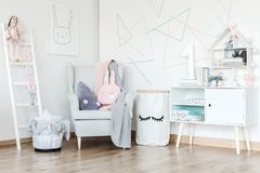 Pastel baby`s room with cupboard. Toy on ladder and pink pillow on grey armchair in pastel baby`s room with cupboard and paper bag for toys royalty free stock photo