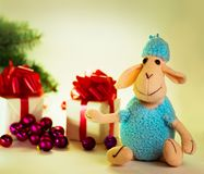 Toy lamb with Christmas balls. And fir paws gifts royalty free stock photography