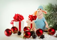 Toy lamb with Christmas balls. And fir paws gifts stock photography