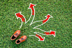 Toy leather shoe on grass field with arrow.jpg Stock Images