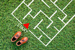 Toy leather shoe on grass field and drawing of maze in the floor Royalty Free Stock Photography