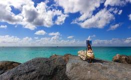 Toy Leprechaun met de vlag van Aruba door de rotsachtige bank van Caraïbisch Se royalty-vrije stock foto