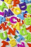 Toy Letters. Composition of many colorful plastic toy letters over white background Stock Photos