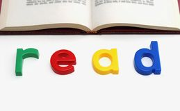 Toy letters spelling Read. A child's toy letters spelling out the word READ under an open book royalty free stock photo