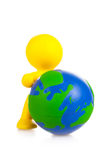 Toy little man rolls forward globe Royalty Free Stock Image