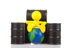 Toy little man sits next on butts to oil the glob stock photo