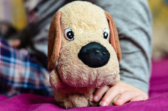 Toy. Little  sick boy sitting at the bed and hodling his toy - little dog Stock Photo