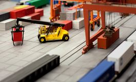 Toy loader carrying a container in a layout of a cargo hub. Layout models of a cargo hub Stock Photos