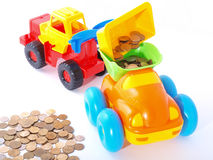Toy loader loads the coin into the truck. Royalty Free Stock Photography