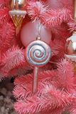 Toy lollipop hanging on the branch of pink Christmas tree Royalty Free Stock Image