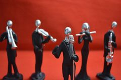 Toy Man with microphone and musicians on red background. Toy Man standing with microphone and musicians on red background stock image