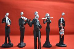 Toy Man with microphone and musicians on red background. Stock Photo