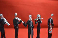 Toy Man with microphone and musicians on red background. Toy Man and musicians standing on red background royalty free stock image