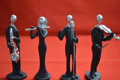 Toy Man with microphone and musicians on red background. Toy man standing with a microphone and musicians on red background stock photography
