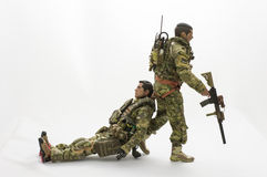 Toy man soldier action figure white background. On the scale miniature realistic toy soldiers helping friends Stock Photos