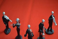 Toy Man with microphone and musicians on red background. Toy Man standing with microphone and musicians on red background royalty free stock image
