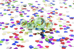 Toy marbles on white background. Surrounded by so many multicolor hearts Stock Photo
