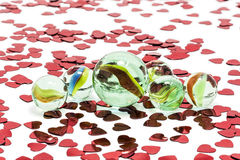 Toy marbles on white background. Surrounded by so many red hearts Royalty Free Stock Photos