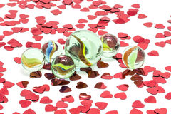 Toy marbles on white background. Surrounded by so many red hearts Stock Photo