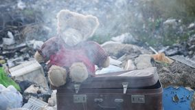 Toy in a mask sits on an old suitcase on a garbage dump