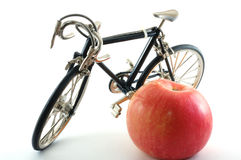 Toy metal bike and apple. Toy bike standing next to red apple Stock Images