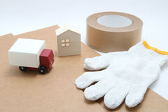 Toy mini car truck, packing tape, card boards, cotton work gloves and house on white background. Royalty Free Stock Images
