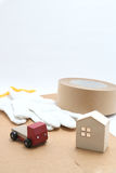 Toy mini car truck, packing tape, card boards, cotton work gloves and house on white background. Stock Image