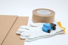 Toy mini car truck, packing tape, card boards, and cotton work gloves on white background. Royalty Free Stock Photo