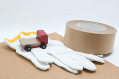 Toy mini car truck, packing tape, card boards, and cotton work gloves on white background. Royalty Free Stock Image