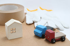 Toy mini car trucks, packing tape, card boards, cotton work gloves and house on white background. Stock Photo