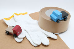 Toy mini car trucks, packing tape, card boards, and cotton work gloves on white background. Stock Photos