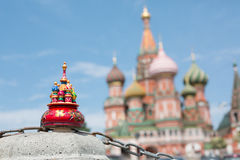 Toy miniature cathedral stands on concrete. Against the Saint Basils Cathedral stock photo