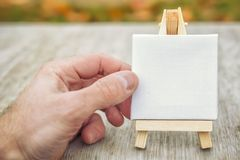 Toy miniature clear white easel in male hand. Easel for write text and drawing. concept of art. Toy miniature clear white easel in male hand. Easel for write royalty free stock photo
