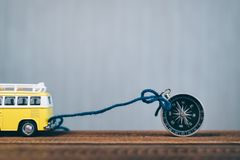 Toy miniature van is tied up to a magnetic compass on a wooden table. concept of travelling, explorer, guidance and transportation. Minivan gps rope trip royalty free stock image
