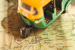 Toy model of auto rickshaw vehicle driving on India map with many cities and the capital in Delhi. Toy model of auto rickshaw vehicle driving on India map with stock photography