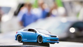 Toy Model Of Modern Car. Close-up footage with focus on a blue toy car  and people moving on blurred background stock video footage