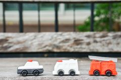 Toy model of police car, ambulance van and electricity and utility service truck for kid. On wooden floor Royalty Free Stock Image