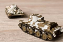 Toy models of Soviet tanks on a wooden table stock photography