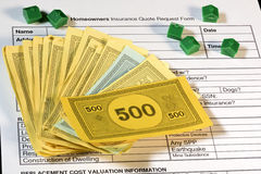Toy money and houses on a home insurance form Stock Photography