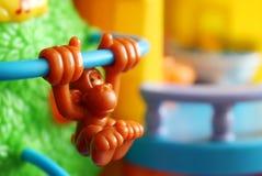 Toy monkey. Hanging on the bar Stock Image