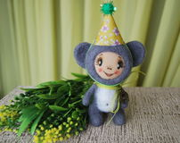 Toy mouse in party hat. Standing about with a branch of yellow f Royalty Free Stock Image