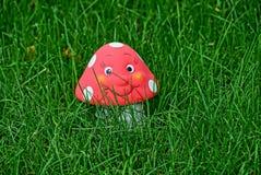 Toy mushroom amanita in green grass stock photo